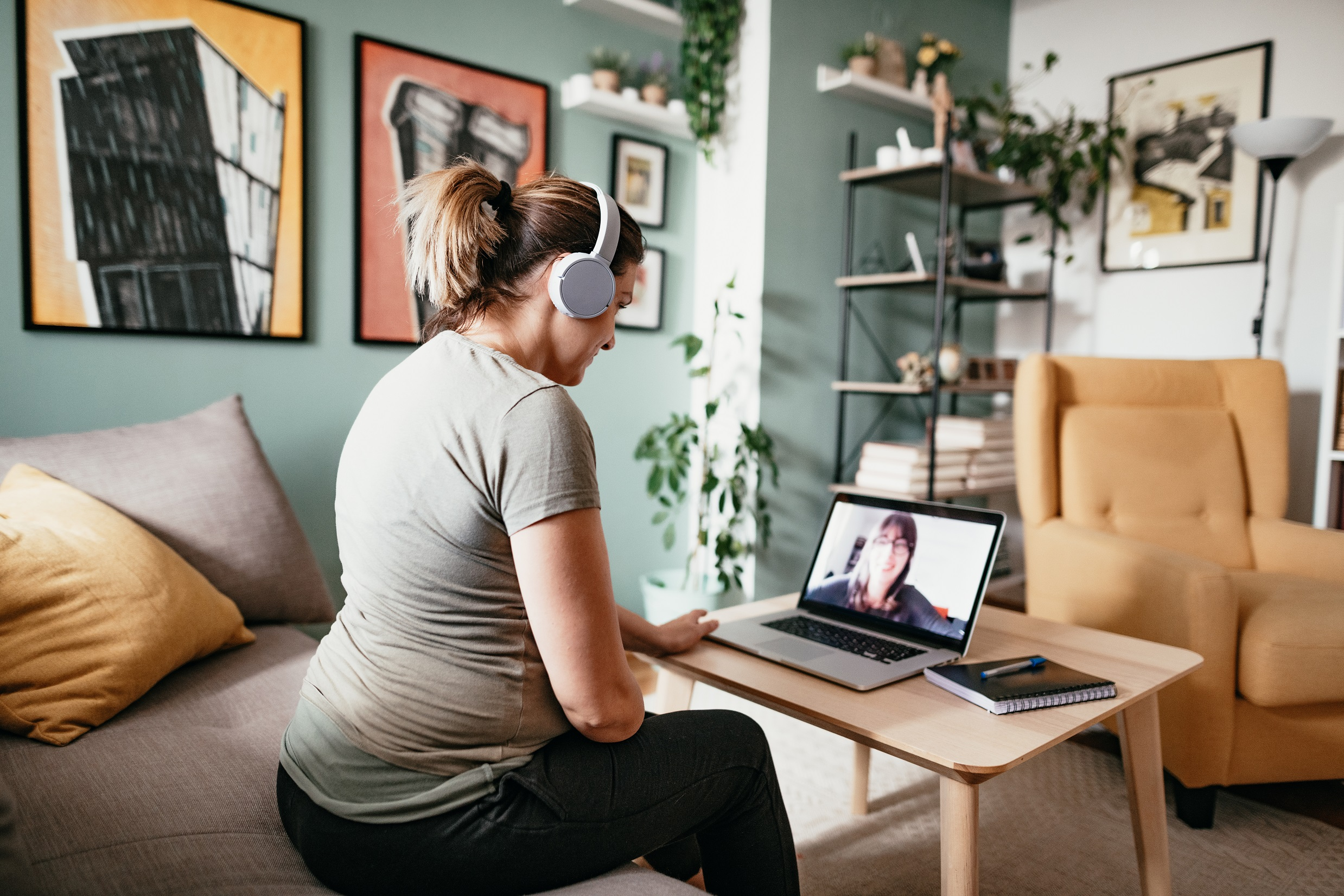 Young woman teleconferencing with friend on laptop
